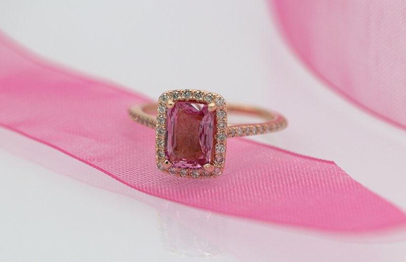 zásnubný prsteň z ružového zlata s ružovým diamantom položený na ružovej stuhe