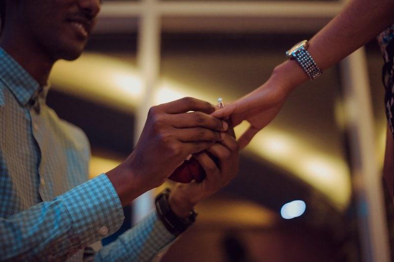 muž kľačiaci pred ženou jej navlieka prsteň na ruku