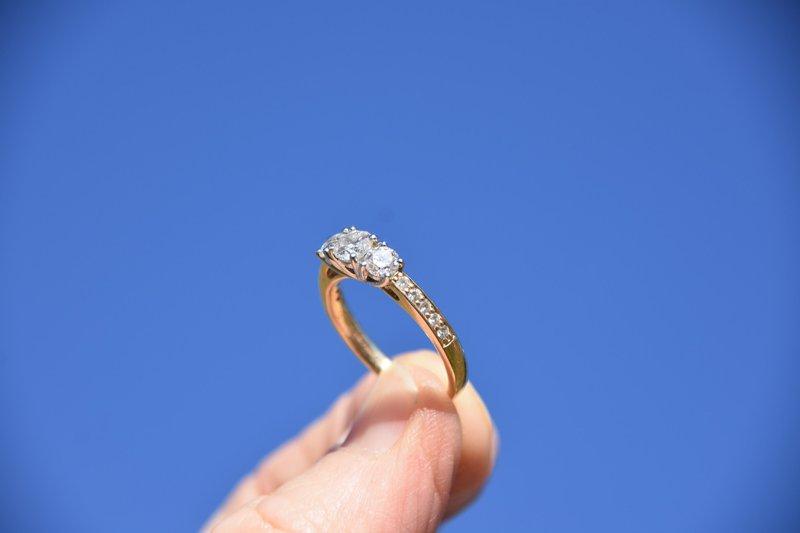 dva prsty držiace zlatý prsteň s diamantom na modrom pozadí