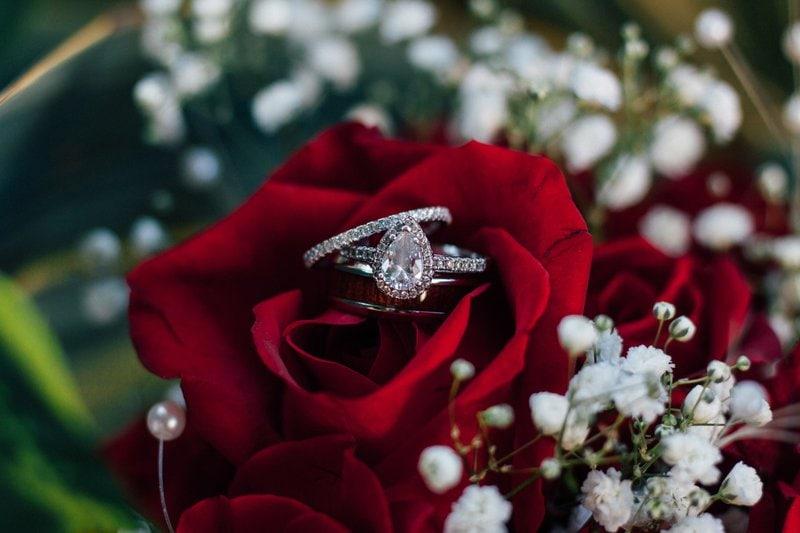 diamantový prsteň položený na kytici z červených ruží lemovanej malými bielymi kvietkami