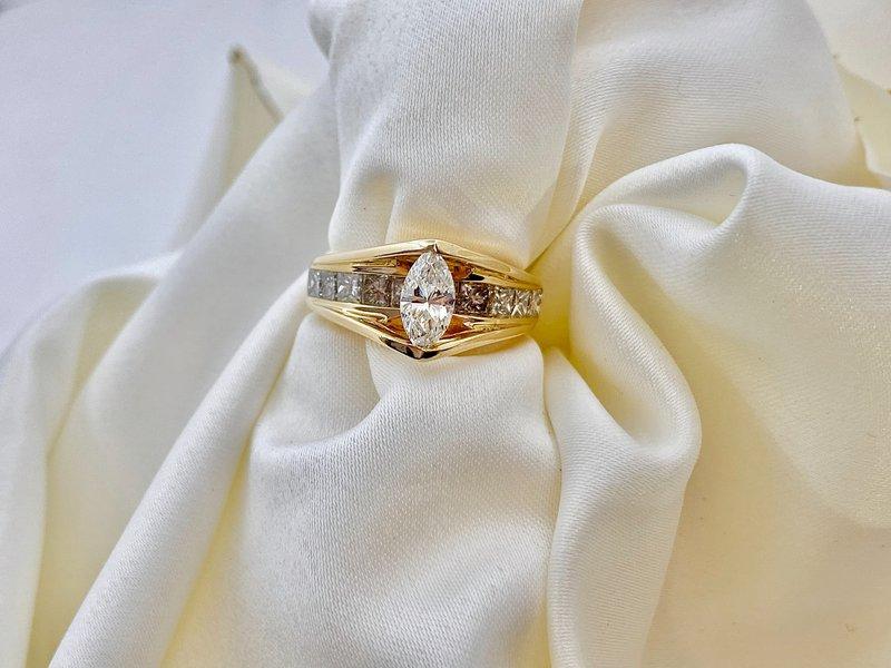 diamantový zásnubný prsteň zo žltého zlata prevlečený cez bielu látku