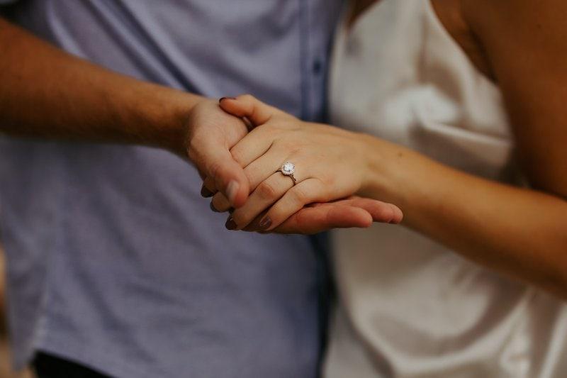 muž držiaci ženskú ruku s diamantovým prsteňom