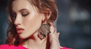zmyselná brunetka s veľkými visiacimi náušnicami v červených šatách - detail tváre