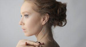mladá žena otočená z profilu s visiacimi náušnicami