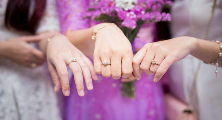 tri ženské ruky ukazujúce diamantové zásnubné prstene