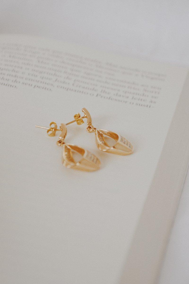 zlaté visiace náušnice položené na otvorenej knihe