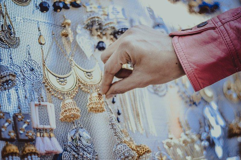 ženská ruka si vyberá náušnice zavesené na priehľadnej sieťke na trhu
