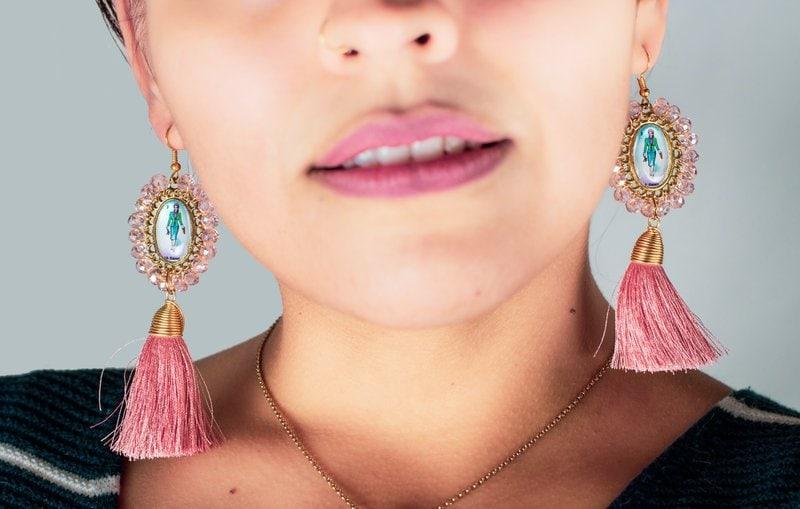 ženská tvár s visiacimi strapcovými náušnicami v ružovej farbe