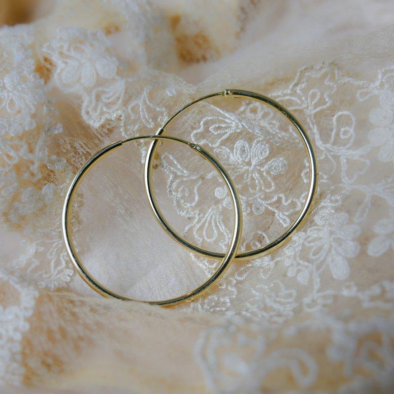 zlaté kruhové náušnice položené na čipkovanej látke
