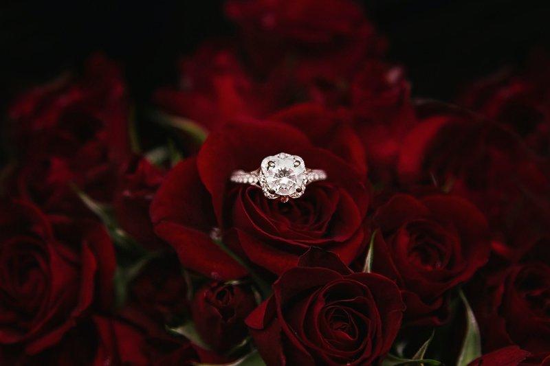 diamantový zásnubný prsteň položený na kytici červených ruží