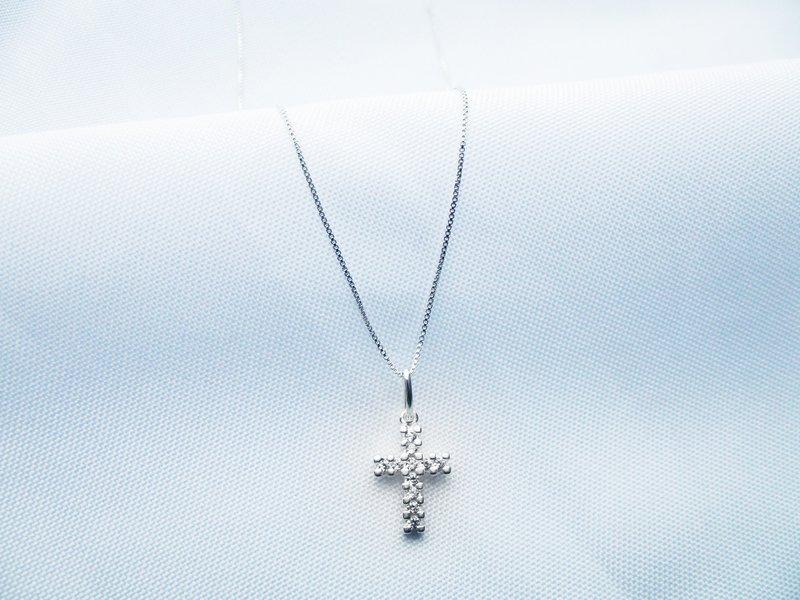 strieborná retiazka s príveskom v tvare krížika na bielom pozadí