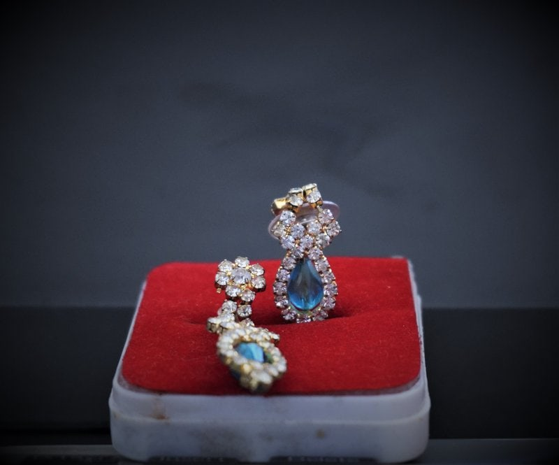 diamantové náušnice uložené na červenom vankúšiku