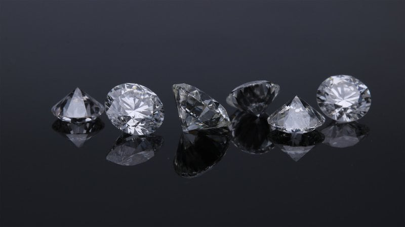 šesť diamantov uložených vedľa seba na tmavomodrom pozadí