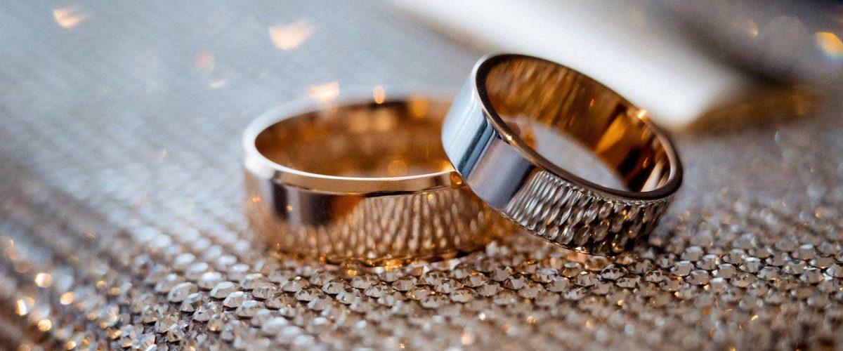 dámska a pánska svadobná obrúčka zo žltého zlata na štrukturovanej textílii