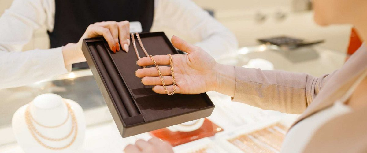 žena si v klenotníctve vyberá retiazku z ružového zlata