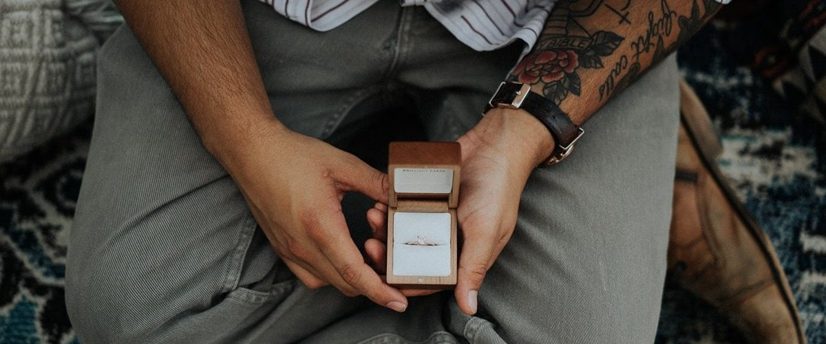 sediaci muž s tetovaním na predlaktí držiaci v rukách krabičku so zásnubným prsteňom
