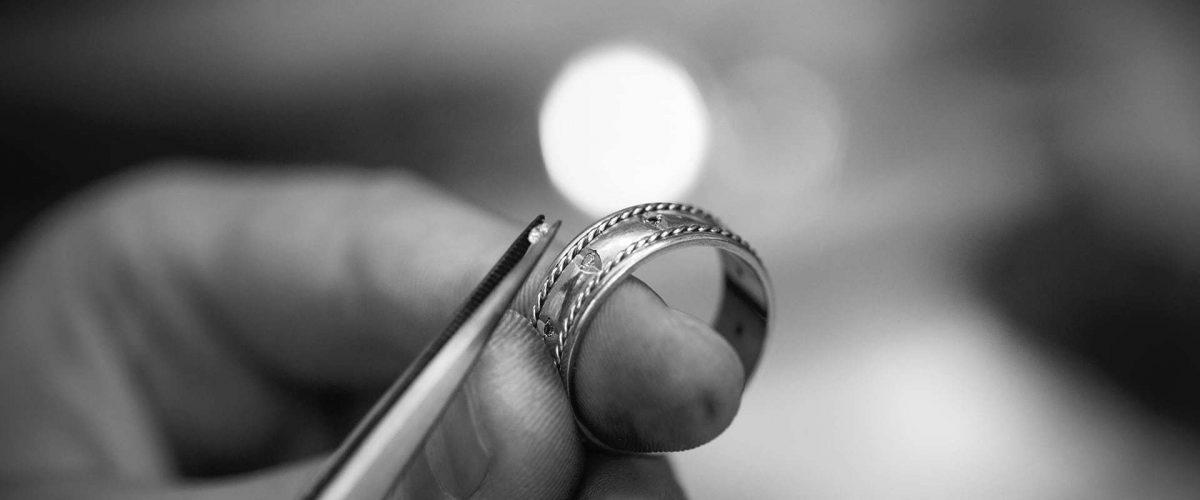 Klenotník osádzajúci diamant na svadobnú obrúčku - čiernobiela fotografia