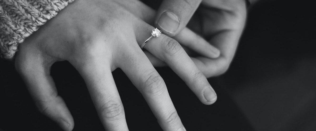 mužská ruka drží ženskú ruku so zásnubným prsteňom na prstenníku na čiernobielom pozadí