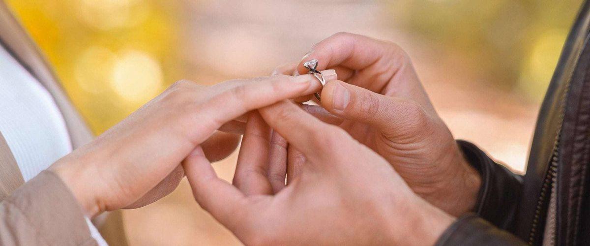 muž navlieka zásnubný prsteň na prstenník ľavej ruky svojej vyvolenej