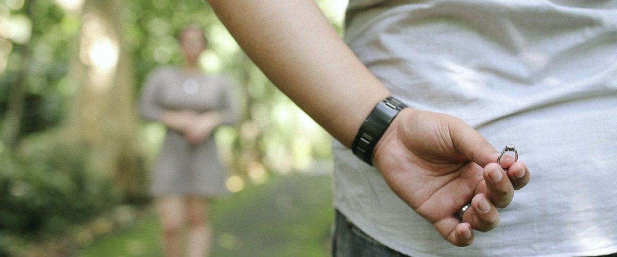 muž drží v ruke zásnubný prsteň za svojim chrbtom