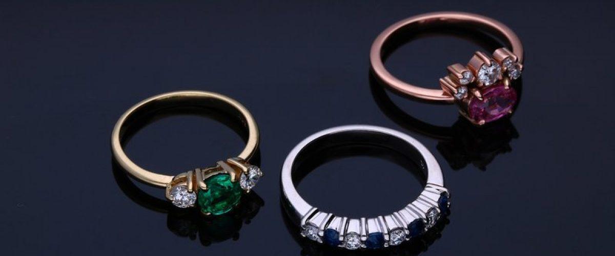 tri prstene zo žltého, bieleho a ružového zlata s farebnými kameňmi na tmavom pozadí