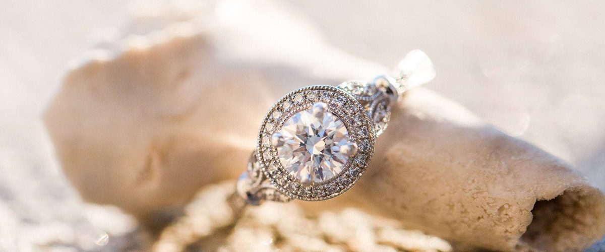 zásnubný prsteň z bieleho zlata v štýle pave vedľa morskej mušle