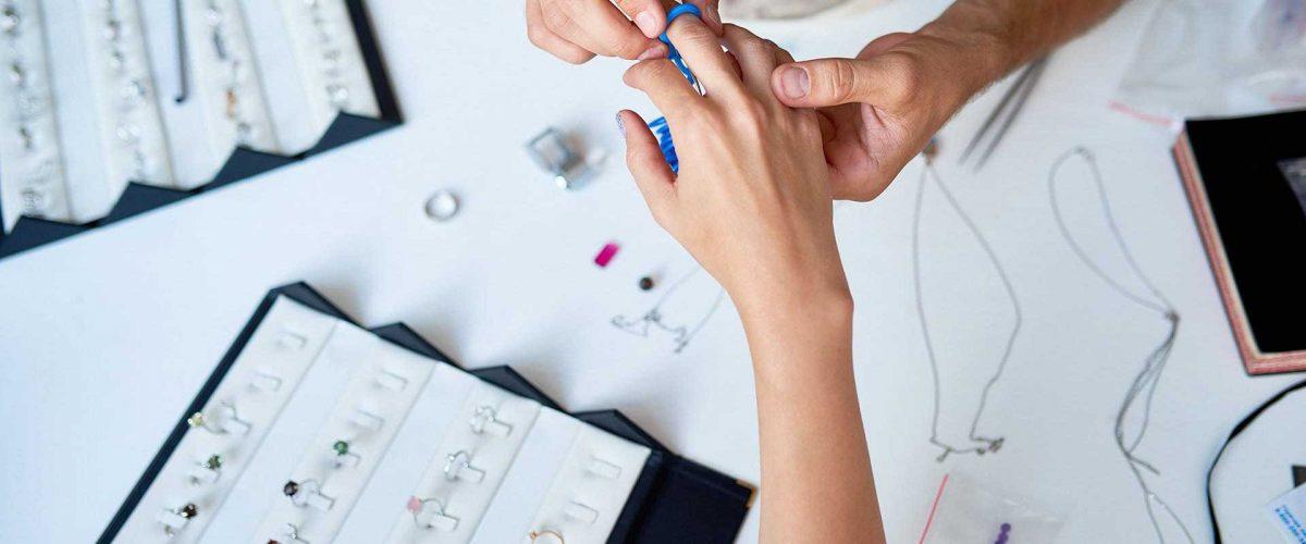 Klenotník meria veľkosť prsteňa na ruke mladej ženy