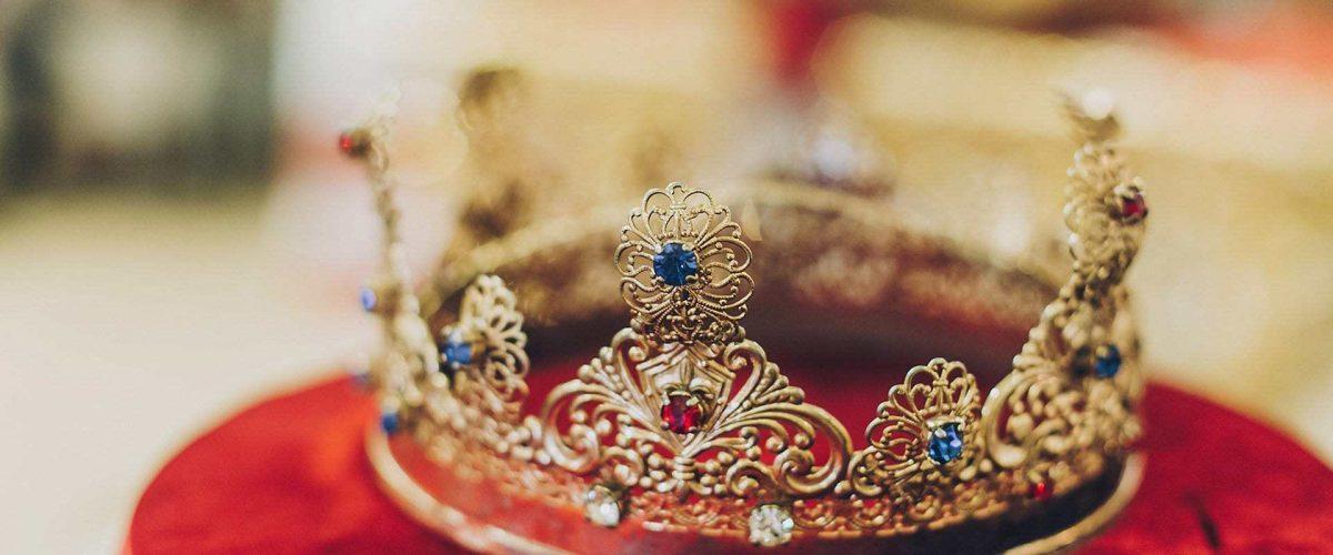 zlatá kráľovská koruna zdobená diamantmi na červenom zamatovom podklade