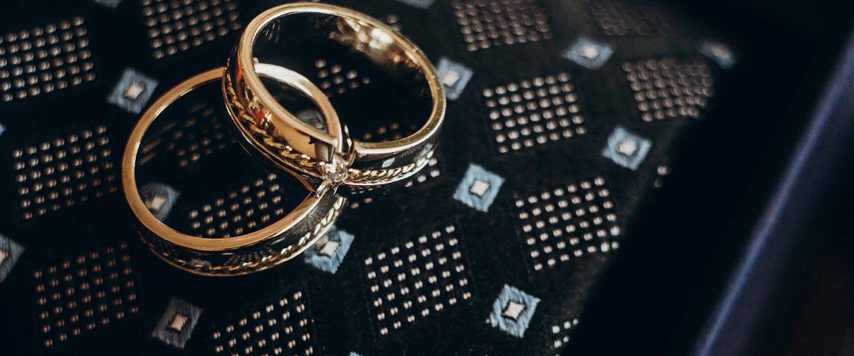 zlaté svadobné obrúčky s diamantmi na tmavom podklade